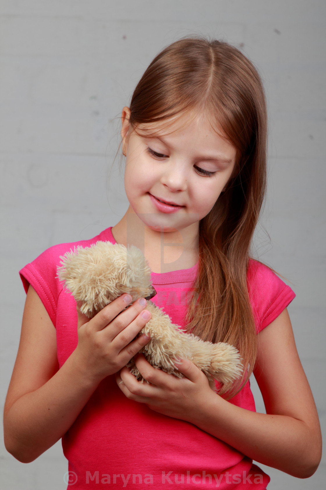 """""""Image of a charming little girl with toy on a gray background"""" stock image"""