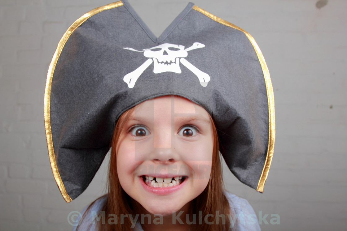 """Portrait of a cute cheerful little girl in a pirate hat hamming and makes a..."" stock image"