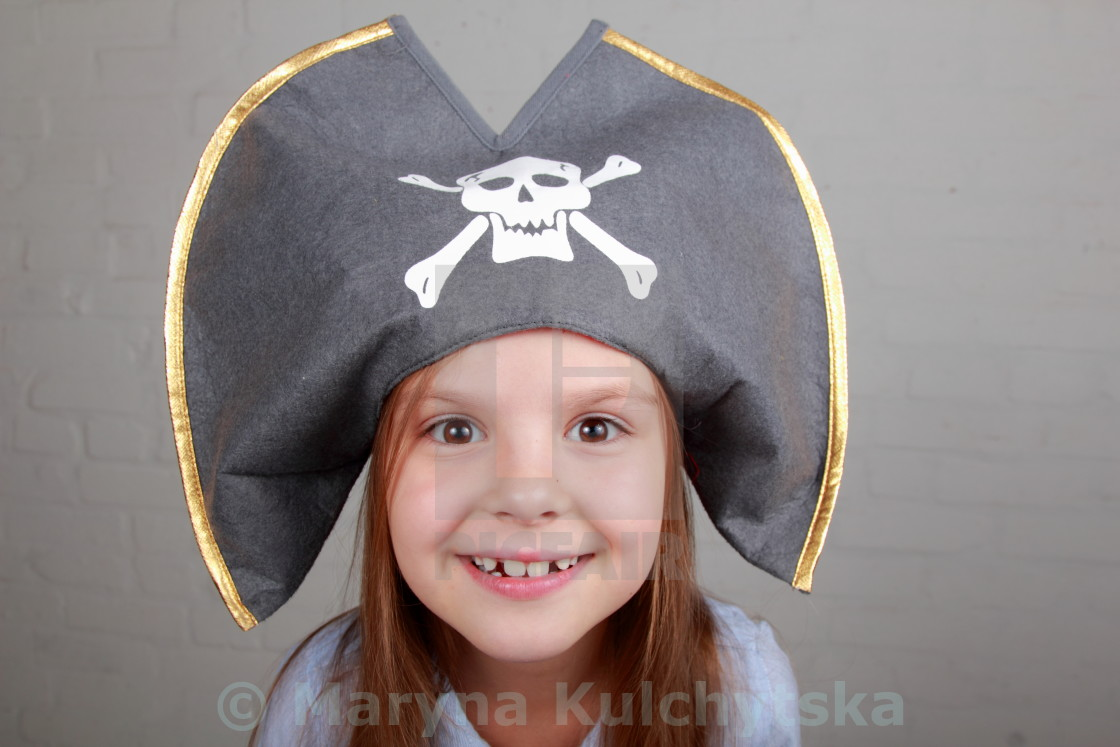 """Terrible pirate girl in shirt and hat on a gray background"" stock image"