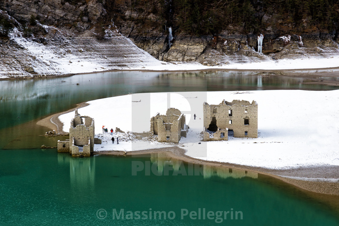 """""""Alpine lake with ruins of old houses partially submerged by water"""" stock image"""