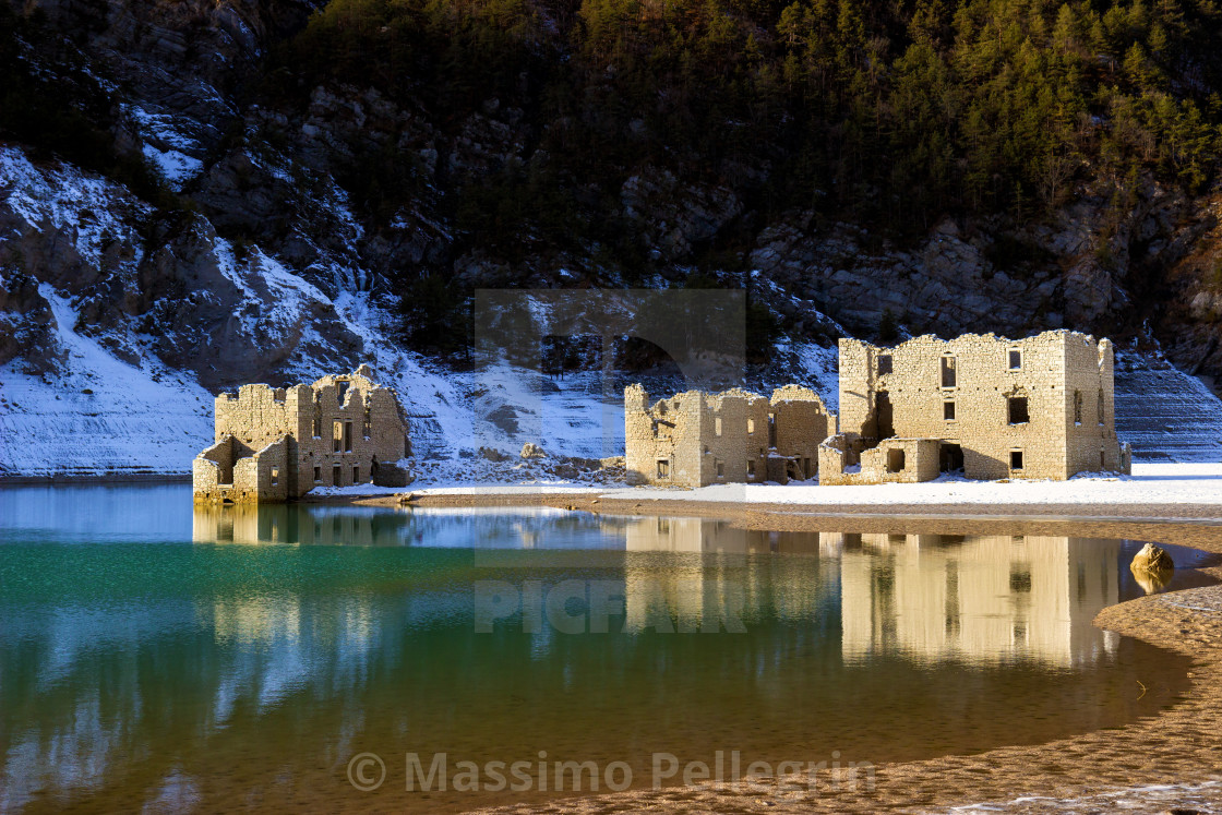 """Alpine lake with ruins of old houses partially submerged by water"" stock image"