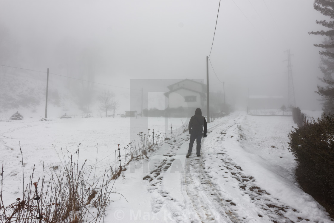 """""""Lonely man walking to home in the winter fog with snowy landscape"""" stock image"""