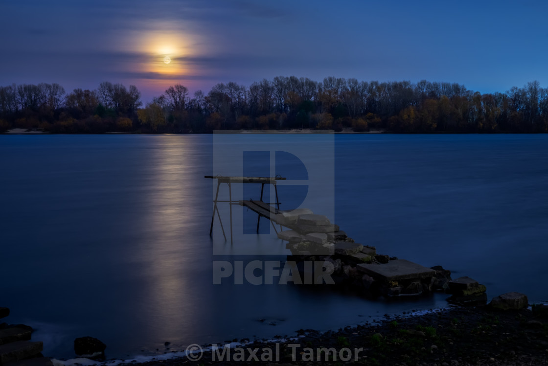 """Real full moon over the autumn forest close to Dnieper river in Kiev, Ukraine. Soft clouds in the dark sky cover partially our natural satellite. A pontoon in the foreground. The water looks like a glossy blue mirror."" stock image"