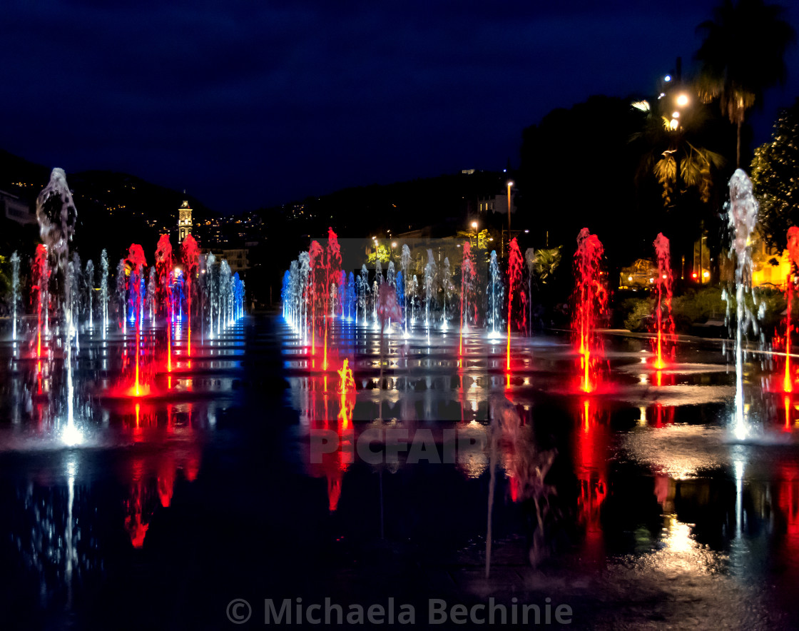 Night shot of colorfully lit water fountains on the Promenade du