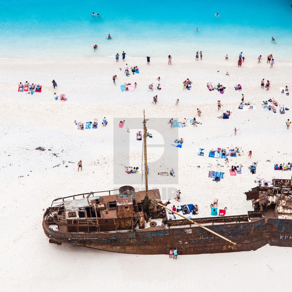 """""""castaways enjoying sunbathing on white sand beach near shipwreck"""" stock image"""