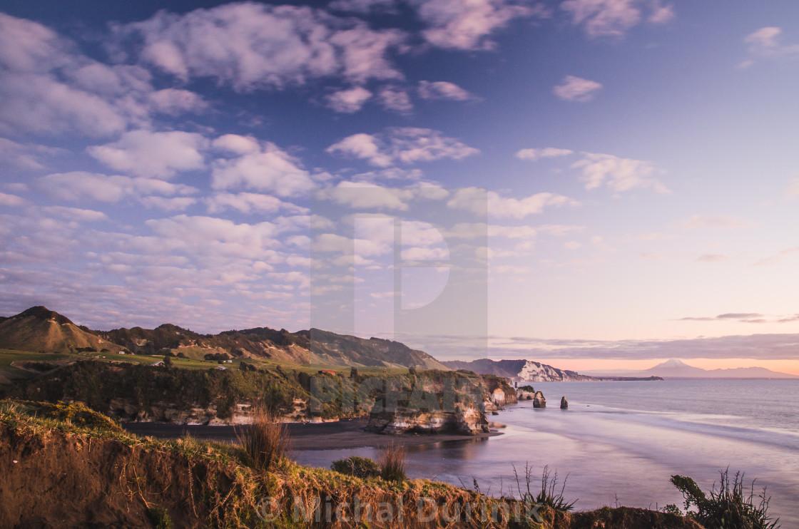 """sunset over sea shore rocks and mount Taranaki, New Zealand"" stock image"