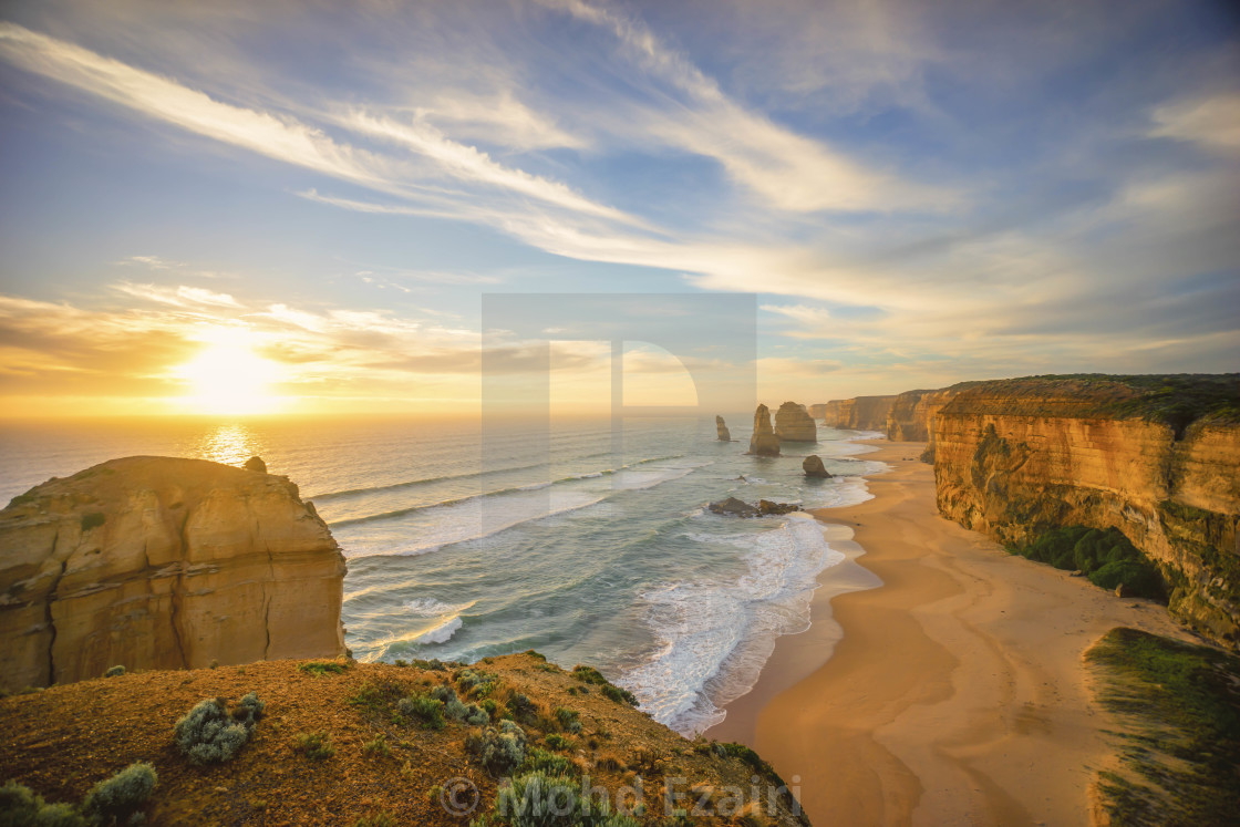 """""""Dramatic sunset sky at unique rock formation along a coastline."""" stock image"""