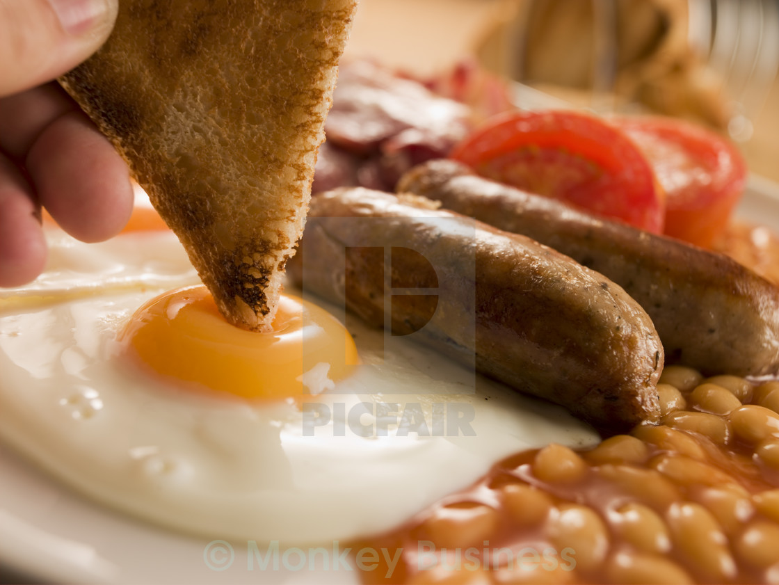 """Dipping Toast into a Fried Egg on a Full English Breakfast"" stock image"