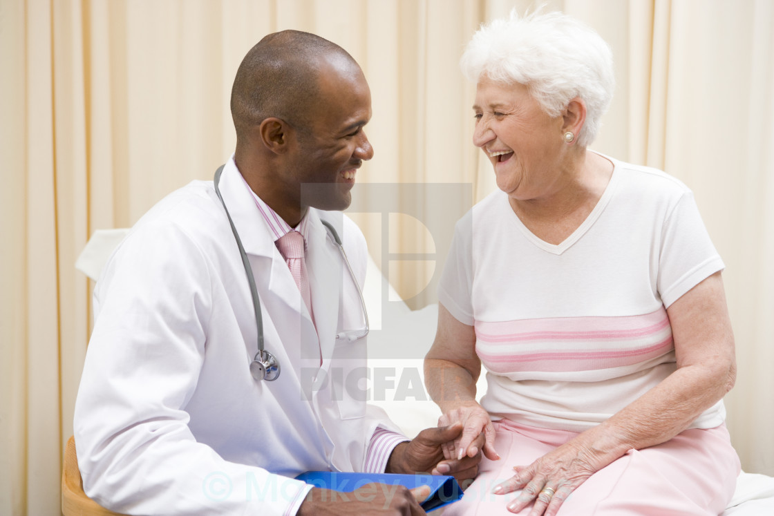 """""""Doctor giving checkup to woman in exam room smiling"""" stock image"""