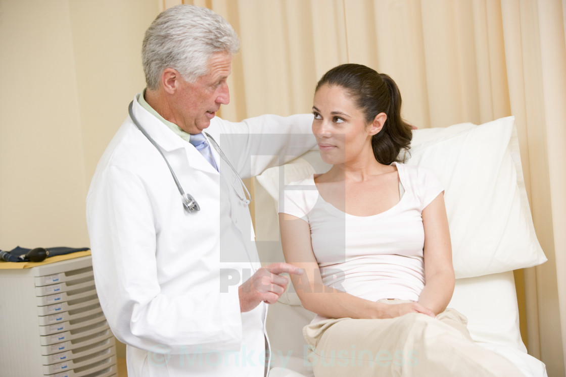 """Doctor giving woman checkup in exam room"" stock image"