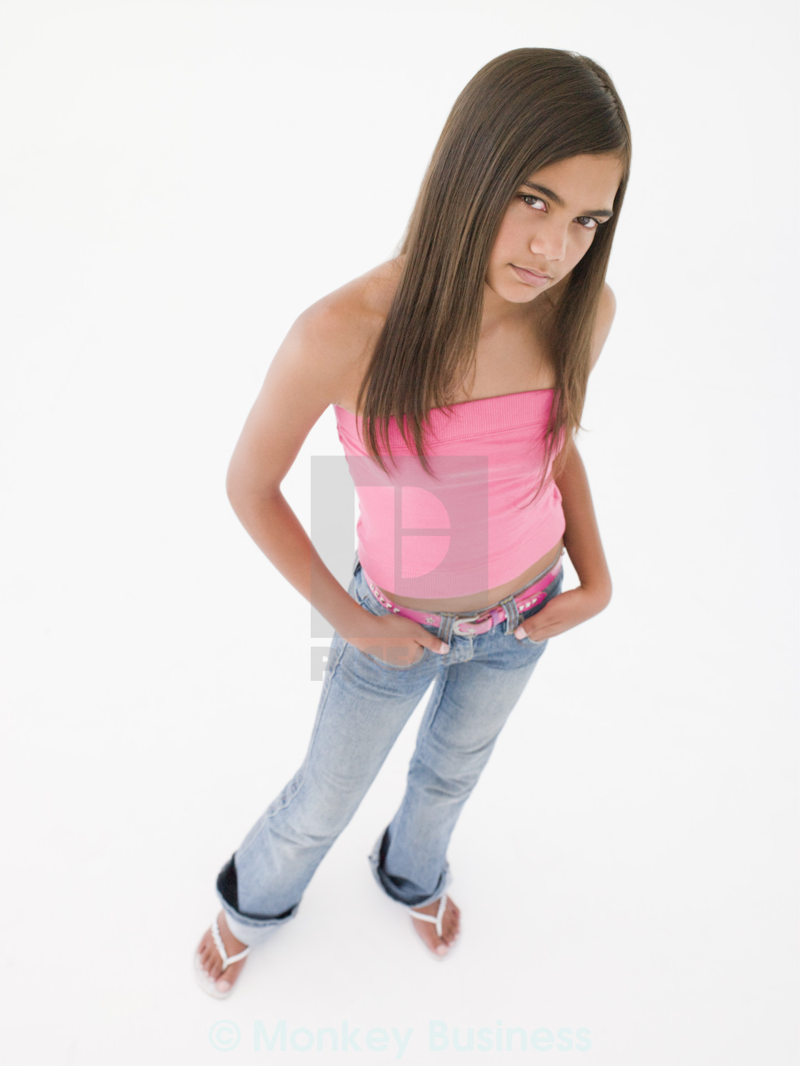 Young girl standing with hands in pockets frowning - License