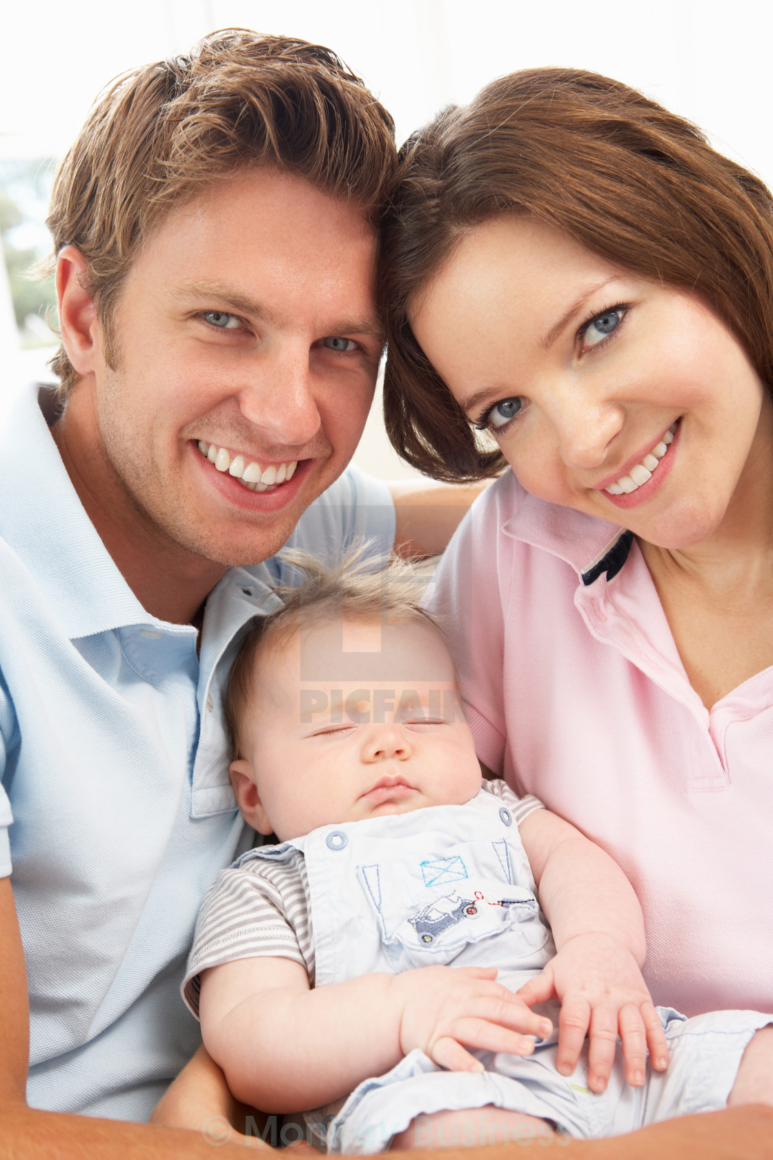 Close up of parents cuddling newborn baby boy at home stock image