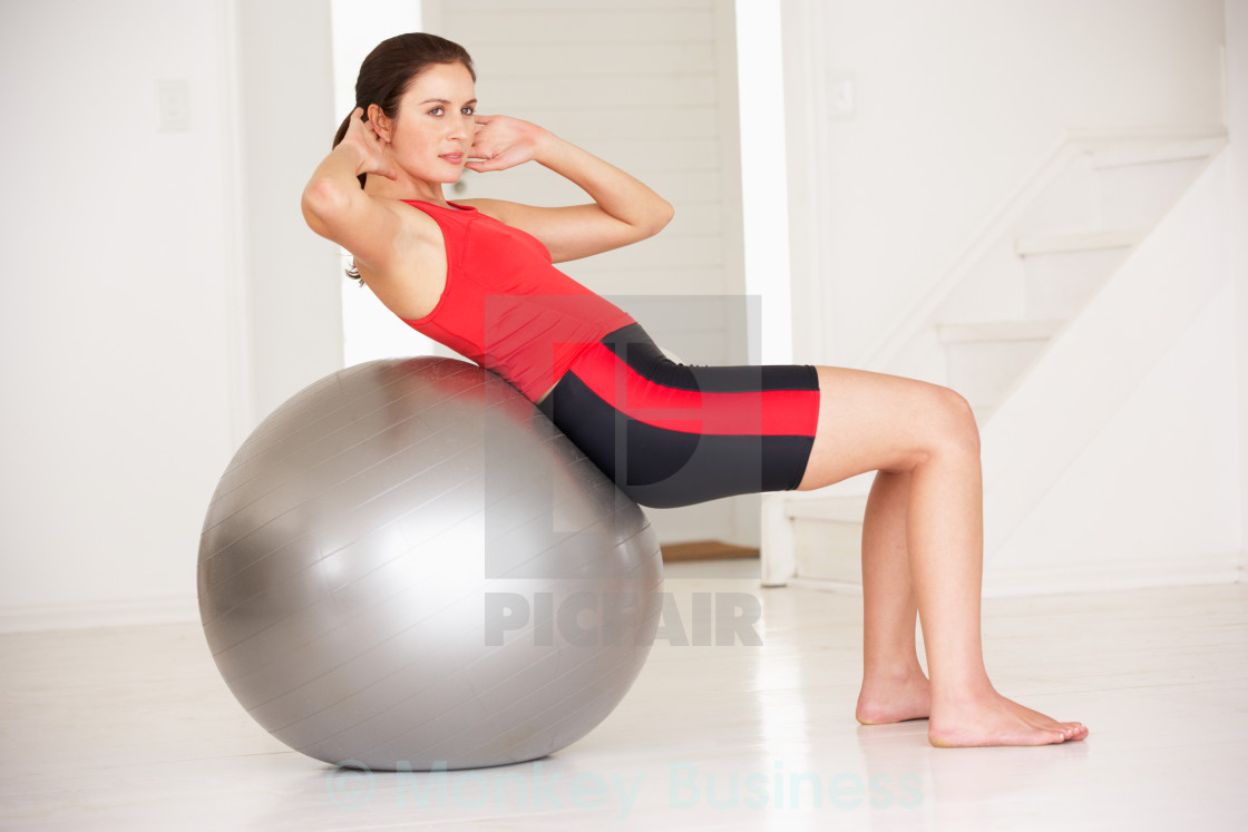 Woman with gym ball in home gym license download or print for