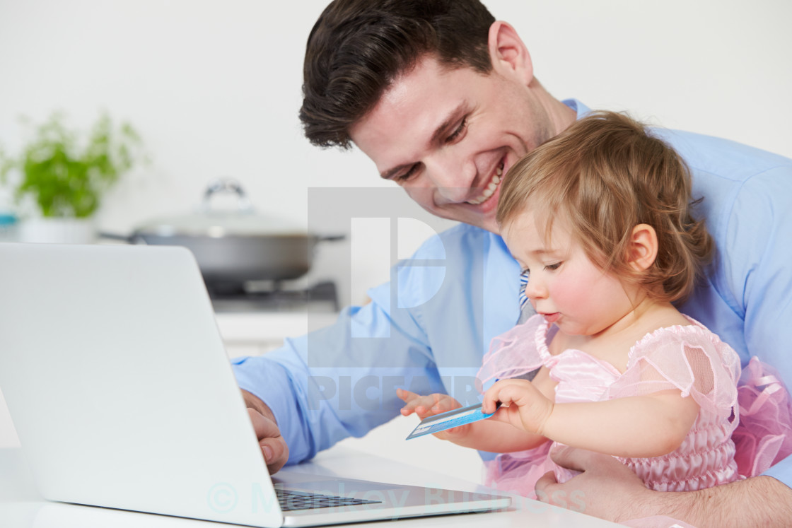 """Father With Child Using Laptop At Home"" stock image"