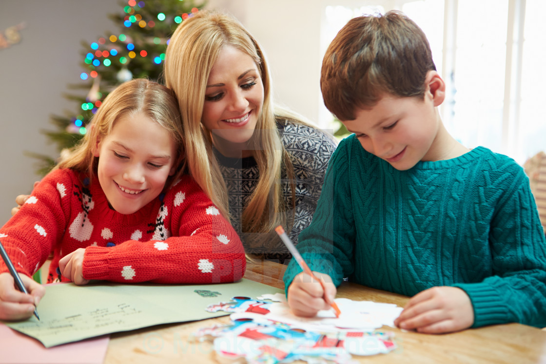 Mother And Children Writing Letter To Santa Together  License For