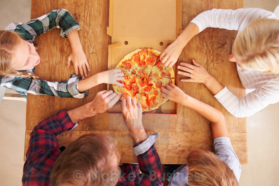"""Family eating pizza together, overhead view"" stock image"