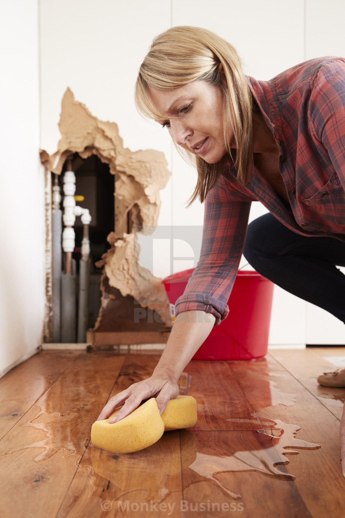 """Woman mopping up water from a burst pipe with sponge, vertical"" stock image"