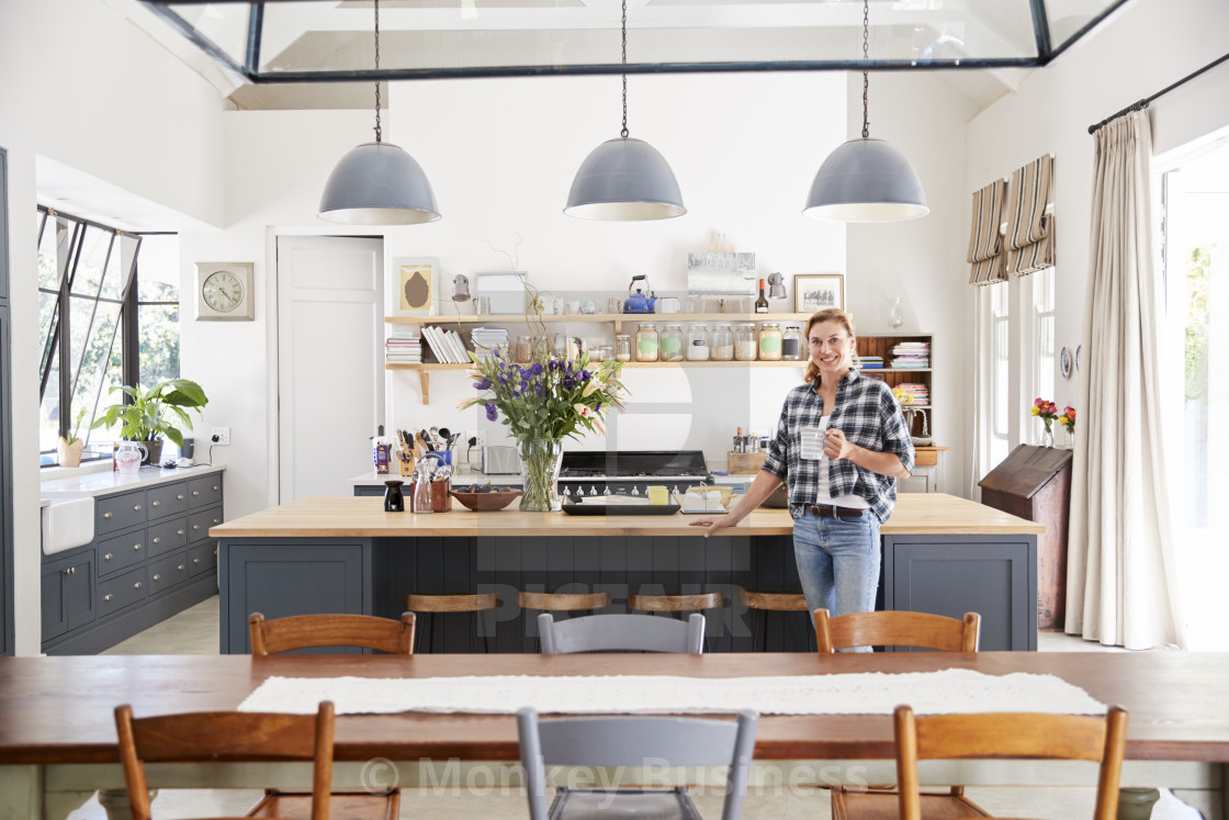 Woman leaning on island in an open plan kitchen dining room ...