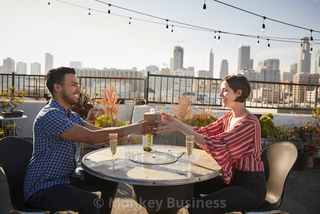 """""""Man Giving Woman Gift As They Celebrate On Rooftop Terrace With City Skyline..."""" stock image"""