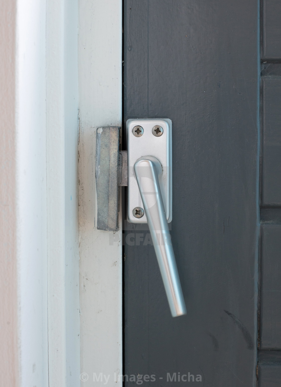 """Close up view of aluminum door window handle"" stock image"