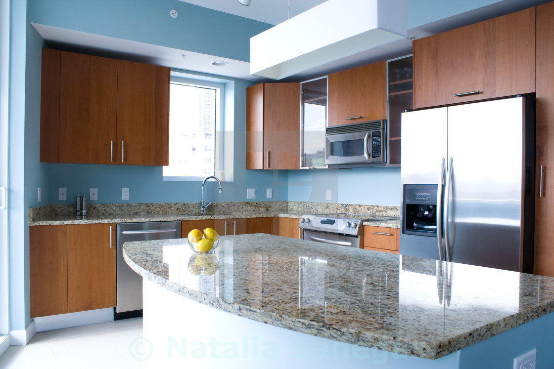 New Modern Kitchen Interior With Island In A Condo Apartment Brightly Lit Light Blue Walls Granite Countertops Stainless Steel Appliances A Bowl Of Lemons On The Countertop License Download Or Print