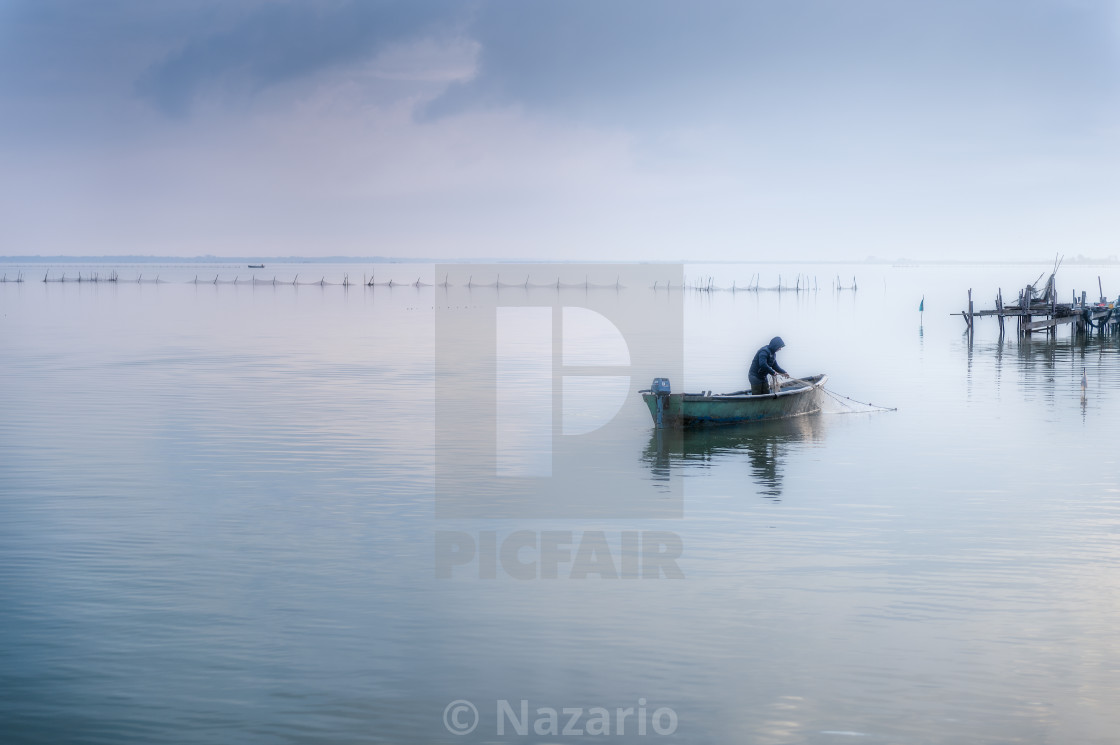 """""""Lesina and its lake. Fisherman in a boat."""" stock image"""