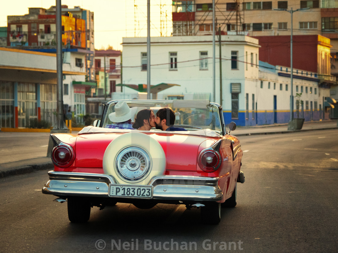 """Couple kissing in Vintage car in Cuba"" stock image"