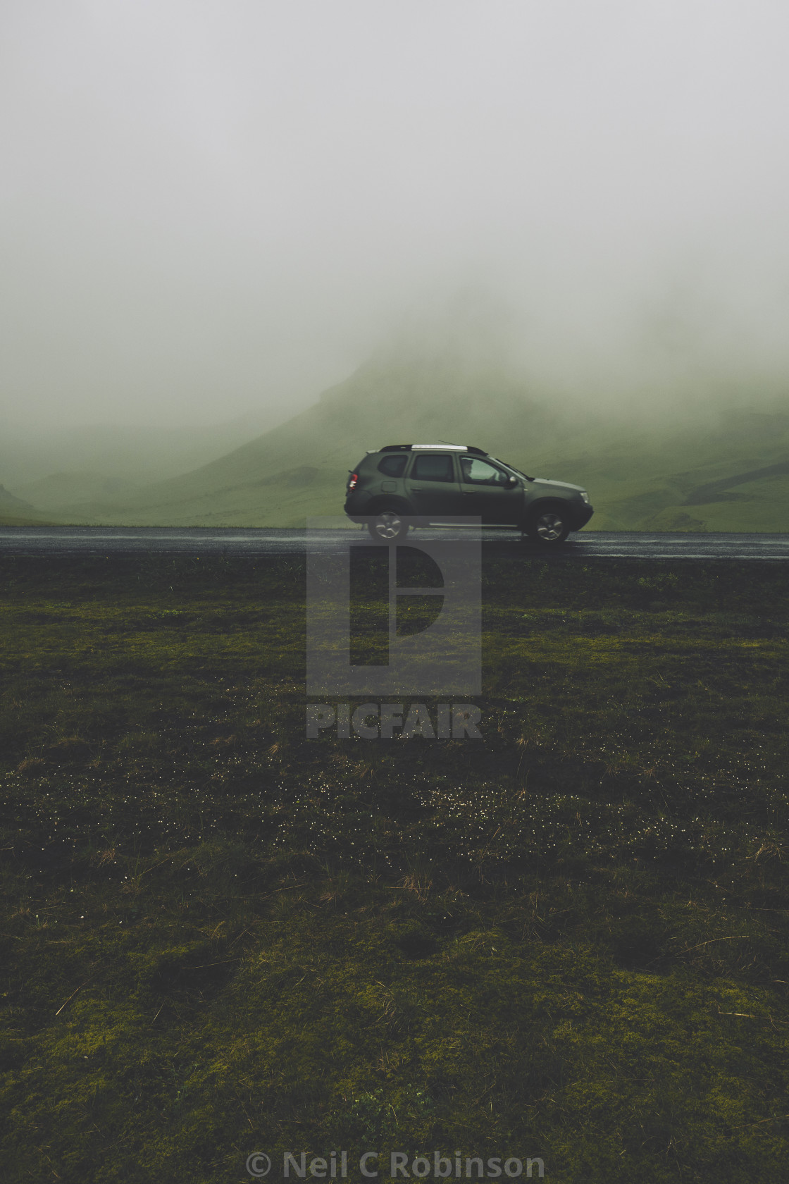 A lone car traveling in a low cloud mountain landscape