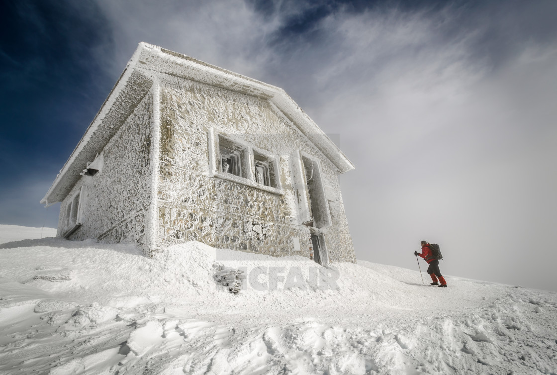 """Mountain climber approaching shelter."" stock image"