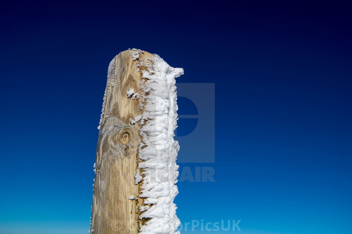 """Frozen Wooden Post Against a Clear Blue Sky"" stock image"