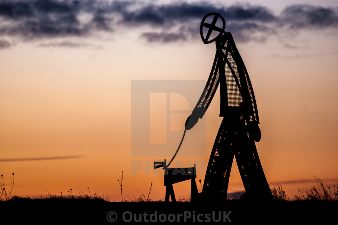 """Man and Dog Metal Sculpture"" stock image"