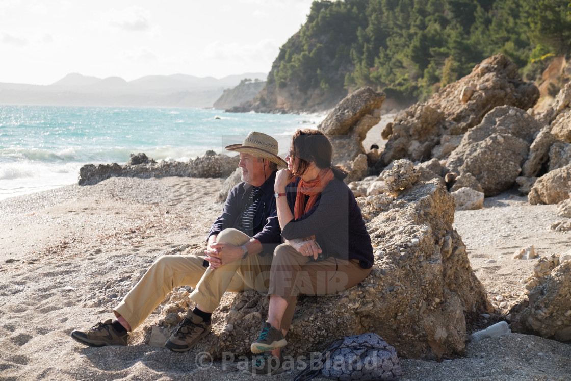 """""""A couple take in the view at Paradissi Beach in Kefalonia, Greece."""" stock image"""