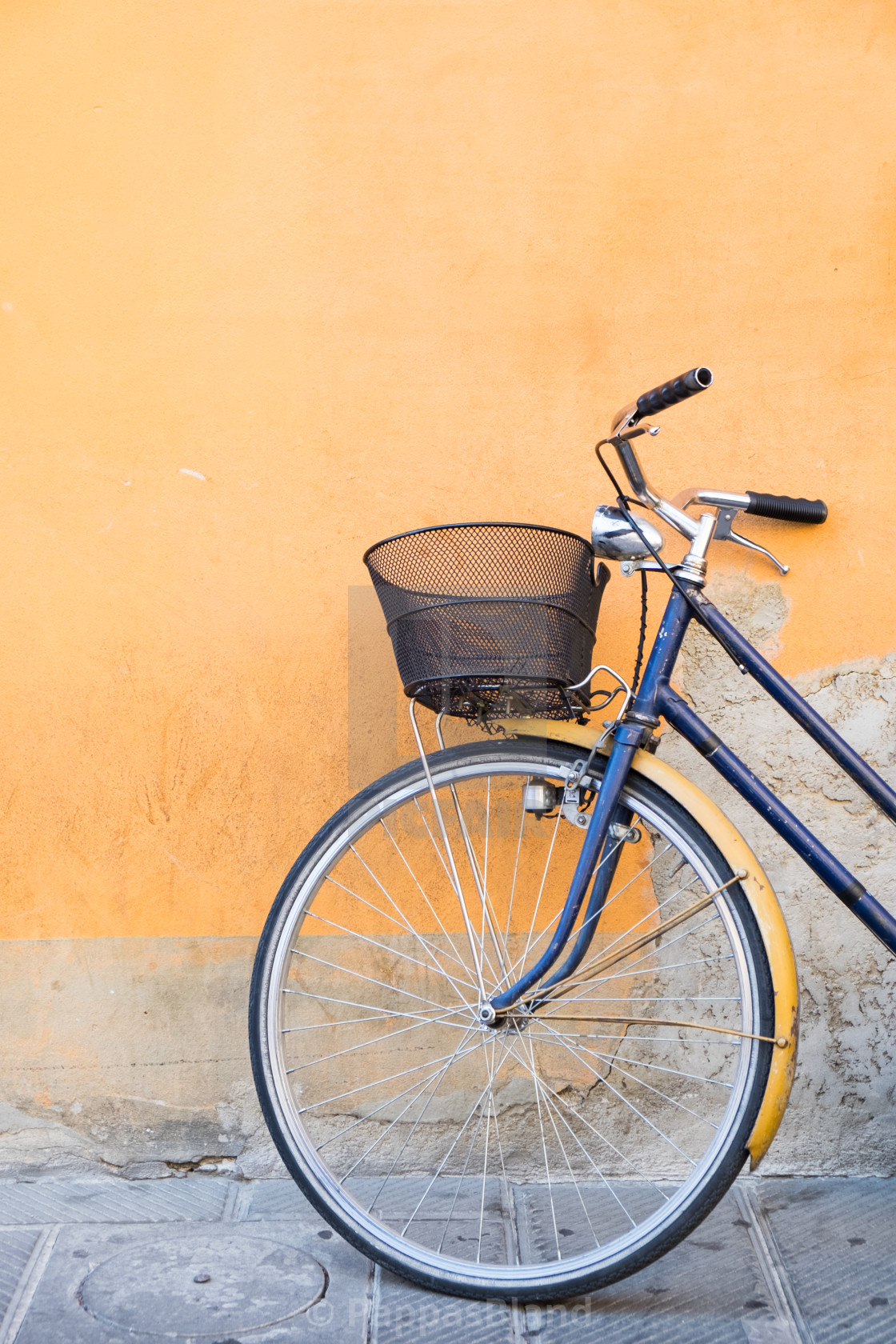 """""""A navy blue bicycle against an orange wall in Pisa, Italy."""" stock image"""