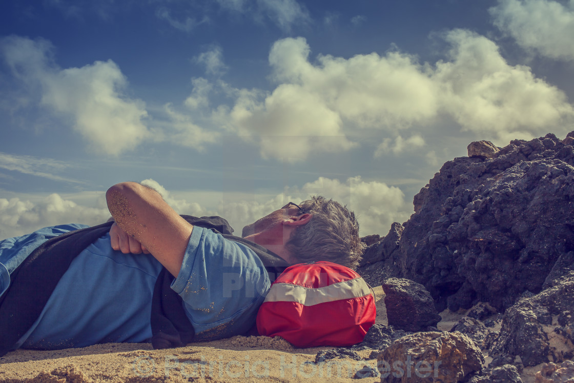 """Man resting on beach"" stock image"