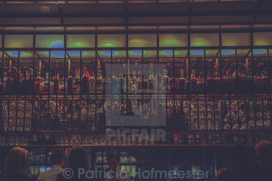 """Rows of hard liquor bottles at a bar"" stock image"