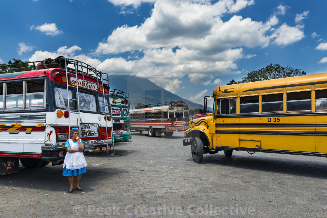 """Woman in a bus terminal with colorful buses in Antigua, Guatemala"" stock image"