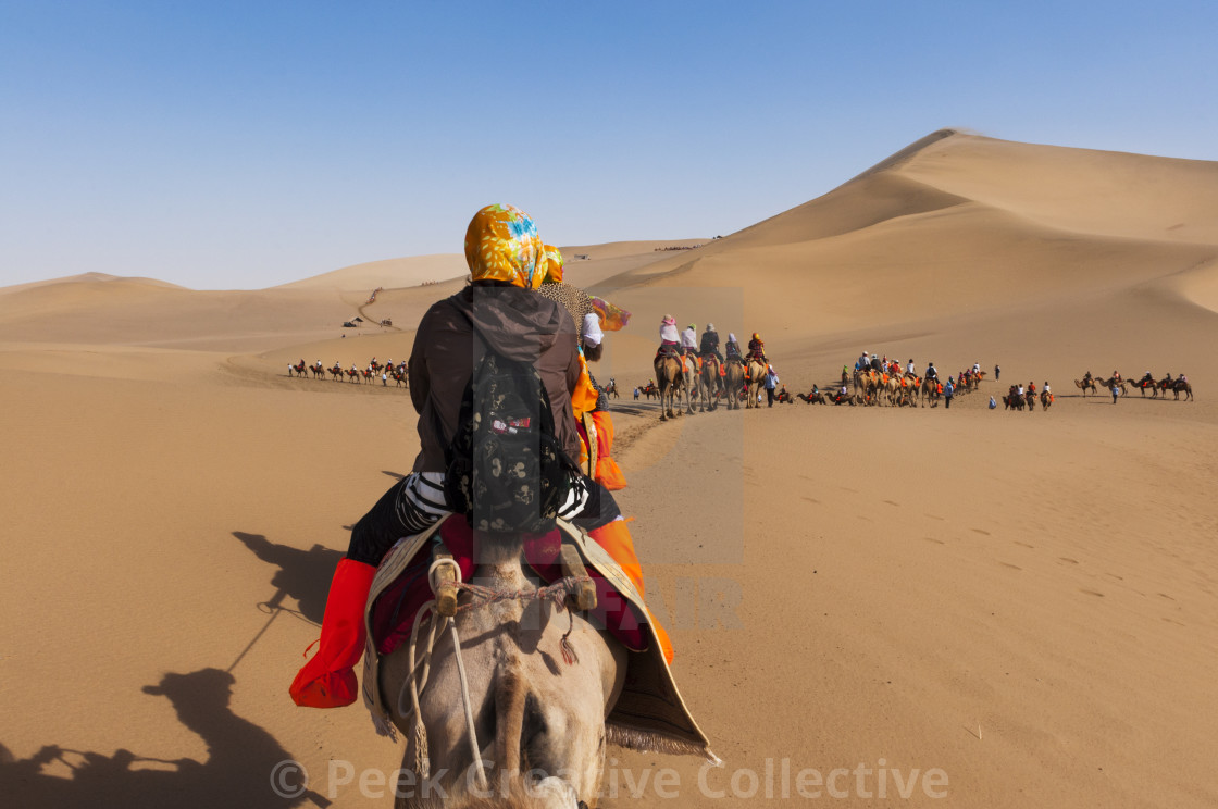 """Dunhuang, China - August 8, 2012: Tourists on a camel caravan in the dunes around the city of Dunhuang, in the ancient Silk Road, in China."" stock image"