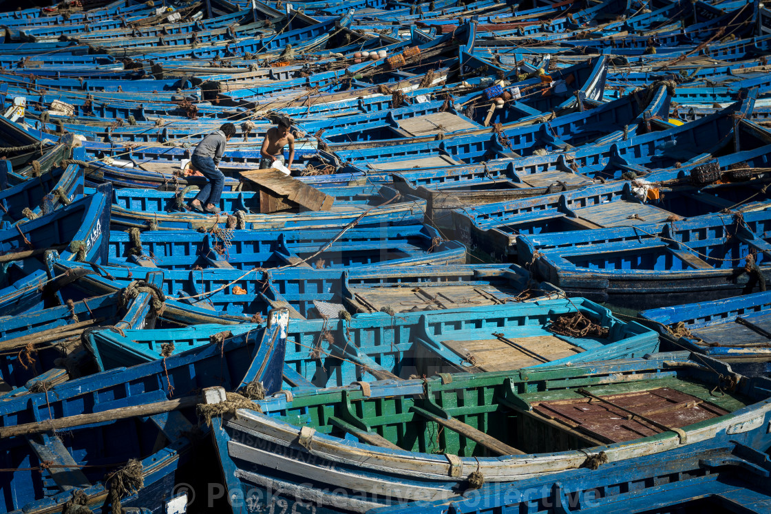 """Essaouira, Morocco - April 14, 2016: Two fisherman working in the traditional blue fishing boats docked in the fishing harbour of Essouria in the Atlantic Coast of Morocco."" stock image"