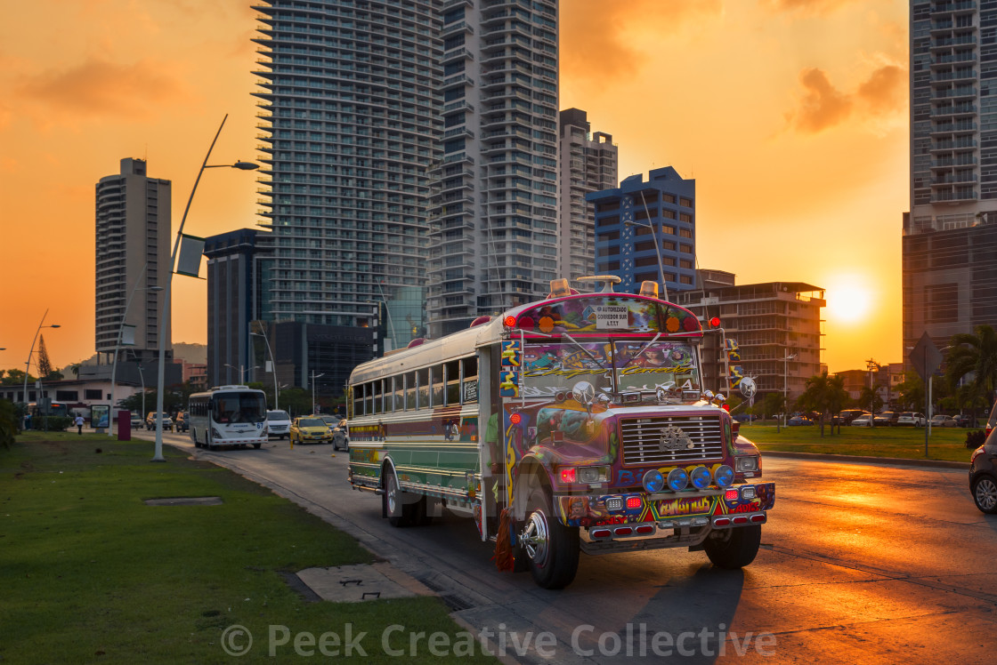 """""""Panama City, Panama - March 18, 2014: A Red Devil bus in Panama City with modern building on the background at sunset, in Panama."""" stock image"""