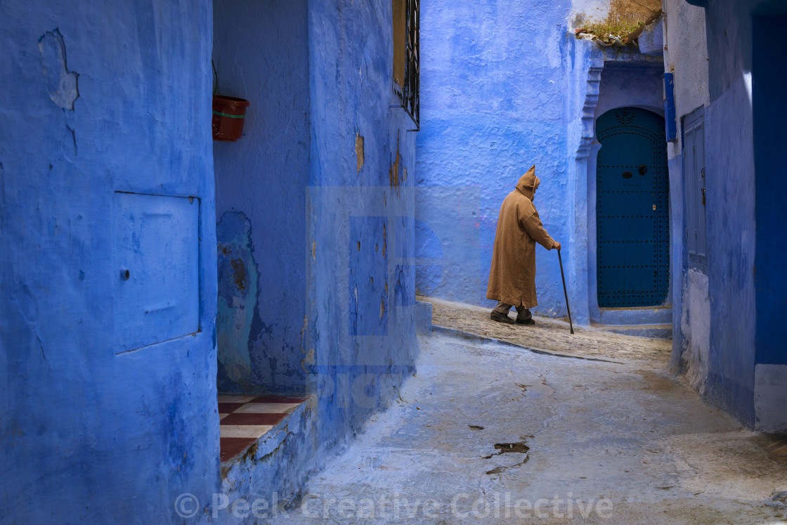 """Chefchaouen, Morocco - April 10, 2016: Moroccan man walking in a narrow street in the town of Chefchaouen in Morocco, North Africa"" stock image"