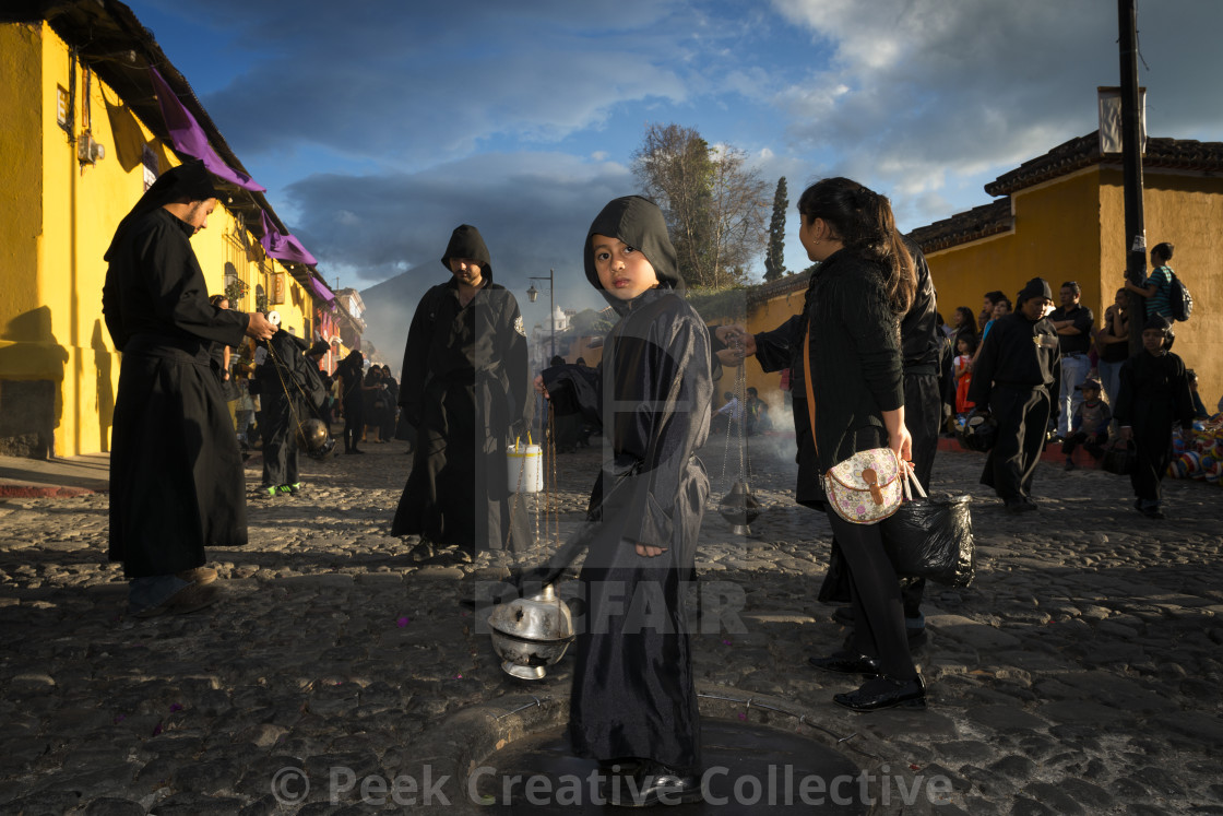 """Antigua, Guatemala - April 19, 2014: Young boy wearing a black robe spreading incense in a street of the city of Antigua during a procession of the Holy Week in Antigua, Guatemala"" stock image"