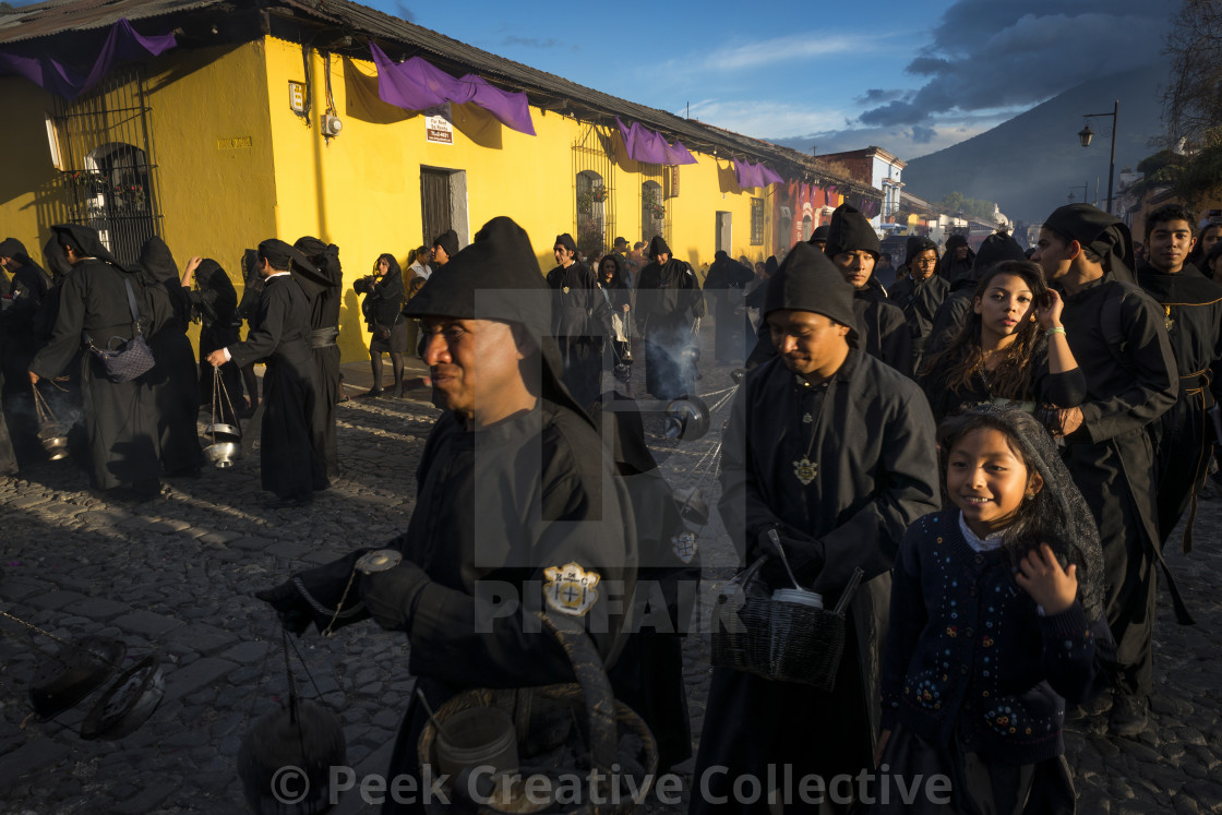 """Antigua, Guatemala - April 19, 2014: People wearing black robes in a street of the old city of Antigua during a procession of the Holy Week in Antigua, Guatemala"" stock image"