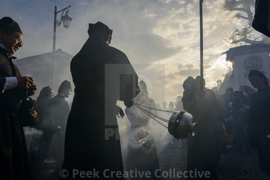 """Antigua, Guatemala - April 19, 2014: Silhouette of men wearing black robes and hoods spreading incense in a street of the city of Antigua during a procession of the Holy Week in Antigua, Guatemala"" stock image"