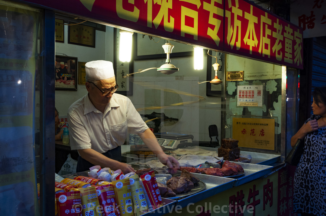 """Xian, China - August 5, 2012: Man selling foof at a a food stall in a street of the Muslim Quarter in the city of Xian in China, Asia"" stock image"