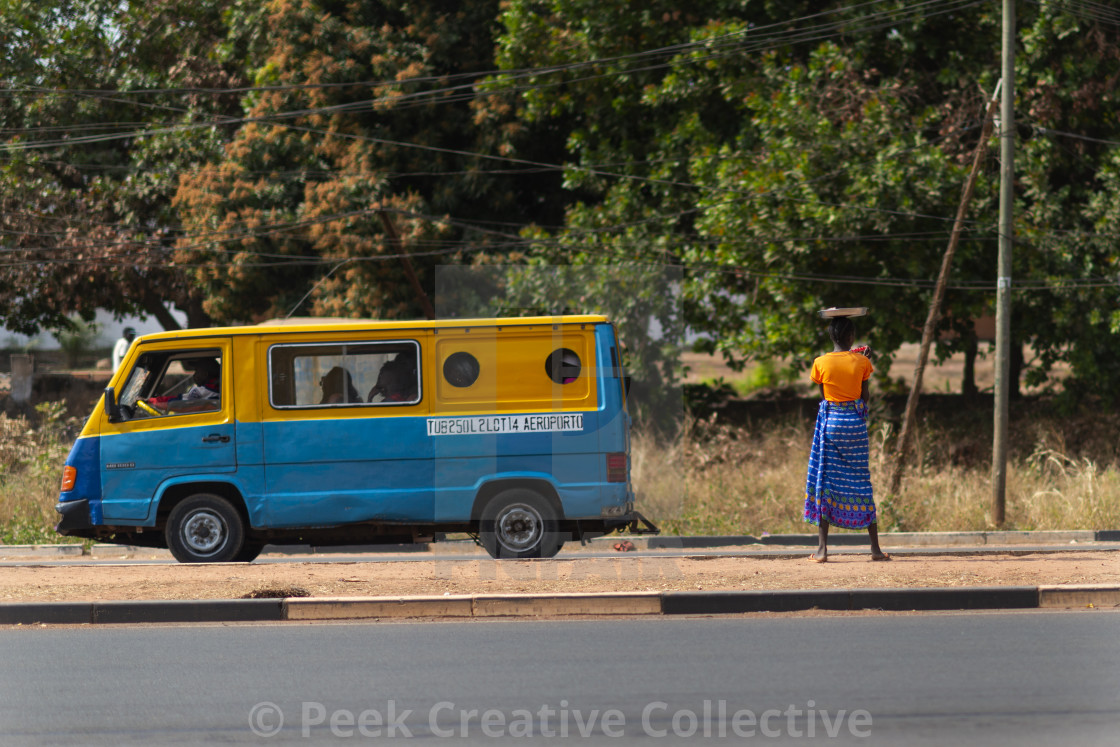 """""""Bissau, Republic of Guinea-Bissau - January 31, 2018: Street scene in the city of Bissau with a woman carrying a tray on her head and a public bus (toca toca) in Guinea-Bissau, West Africa"""" stock image"""