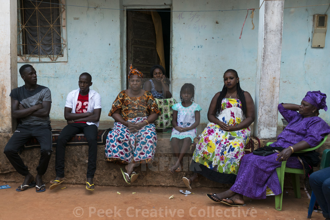 """Bissau, Republic of Guinea-Bissau - January 31, 2018: Family sittting in front of their house at the Cupelon de Cima neighborhood in the city of Bissau, Guinea Bissau"" stock image"