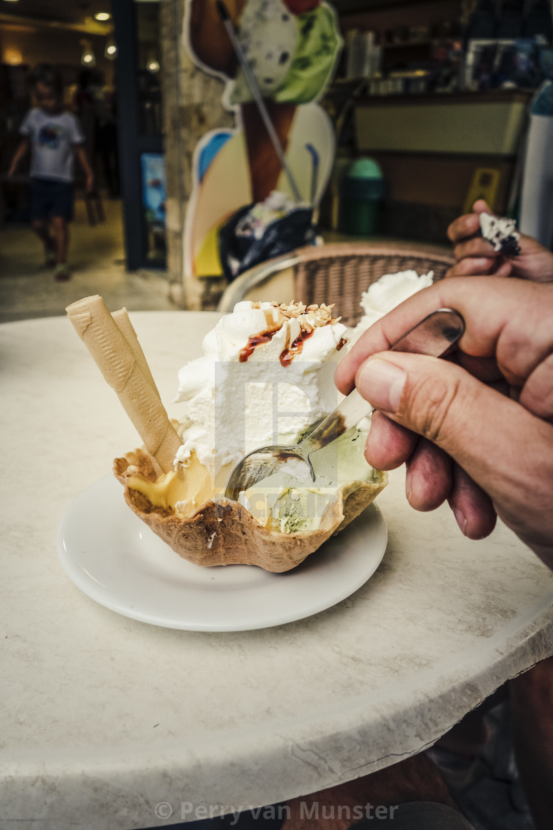 """Hand with spoon reaching for waffle filled with Ice cream, Italian gelato, Spain"" stock image"