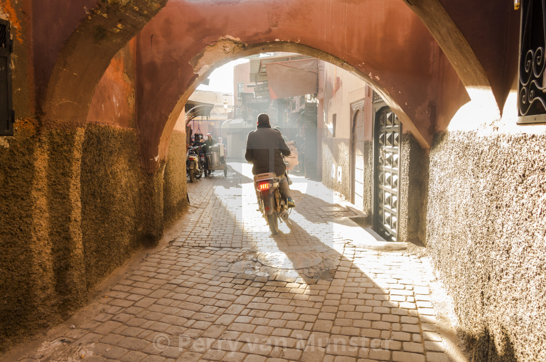 """Scooter drives through smokey street in the Medina of Marrakech, Morocco."" stock image"