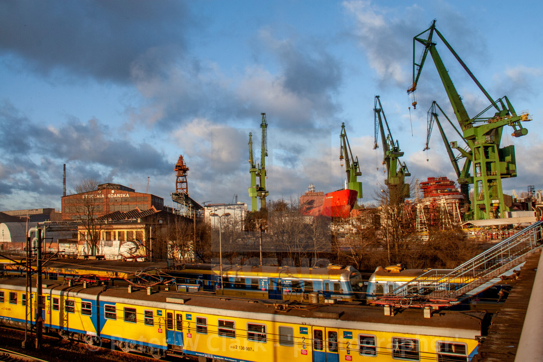 Gdansk, Poland, Shipyard Cranes and Steelworks., Partially built ship in background and electric train carriages to foreground.