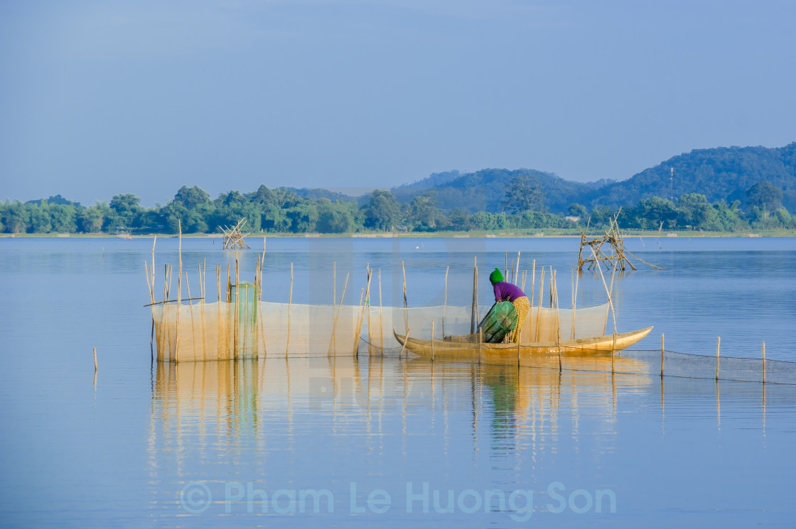 """E De Woman on dugout boat checking her fishing net on lake"" stock image"